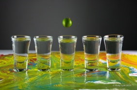 Five shot glasses with olive in mid air above the glass on background with paint