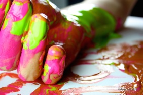 Single hand covered in pink and yellow deep paint lying on a table